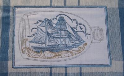 détail bateau dans bouteille brodé sur torchon