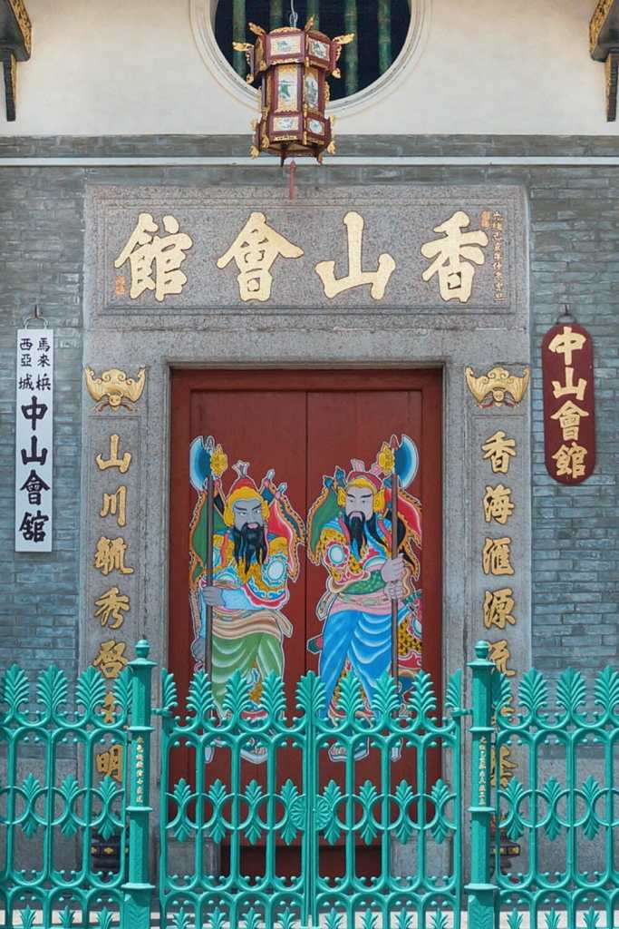 Chinese temple door with green railings and Chinese figures on the door