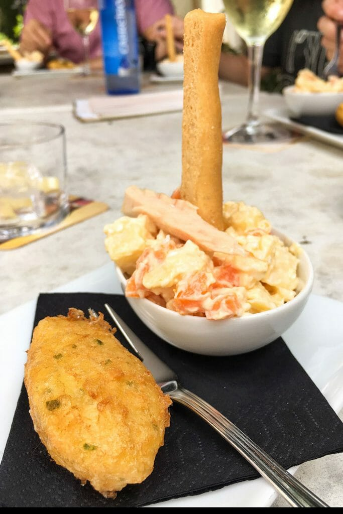 Cod fritter with russian salad in a small white bowl with a bread stick
