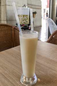 Horchata de chufa in a long glass with straw in a cafe in Valencia