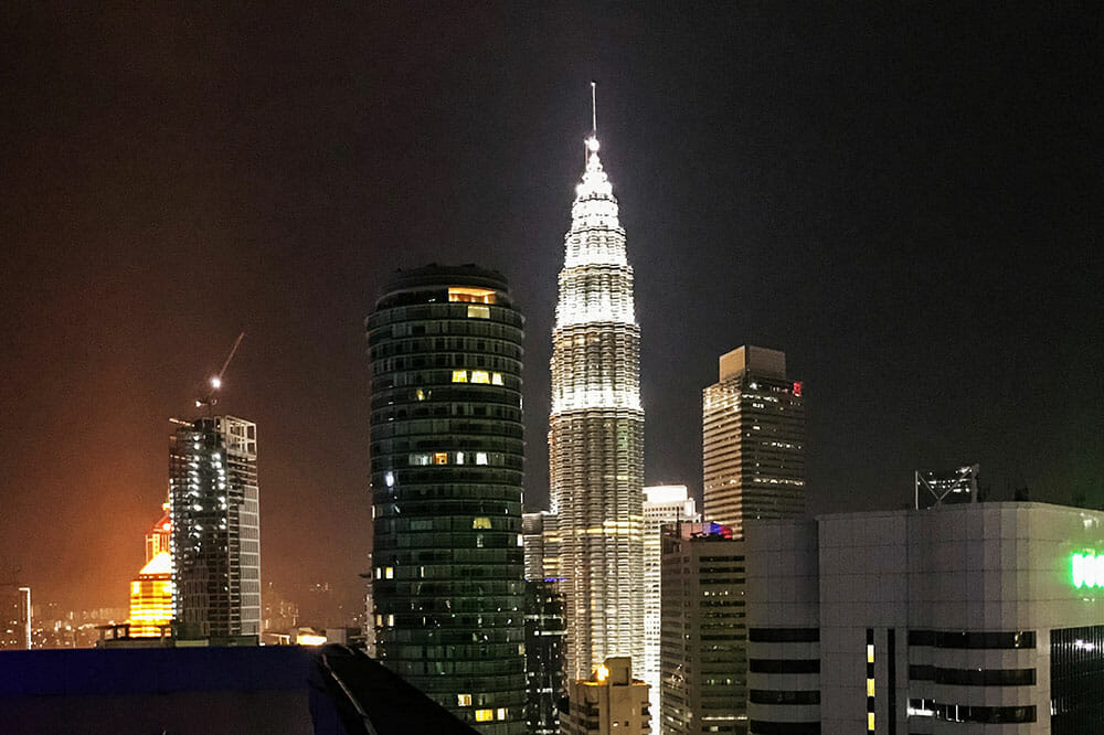 Night view of Petronas Towers lit up and surrounded by other buildings