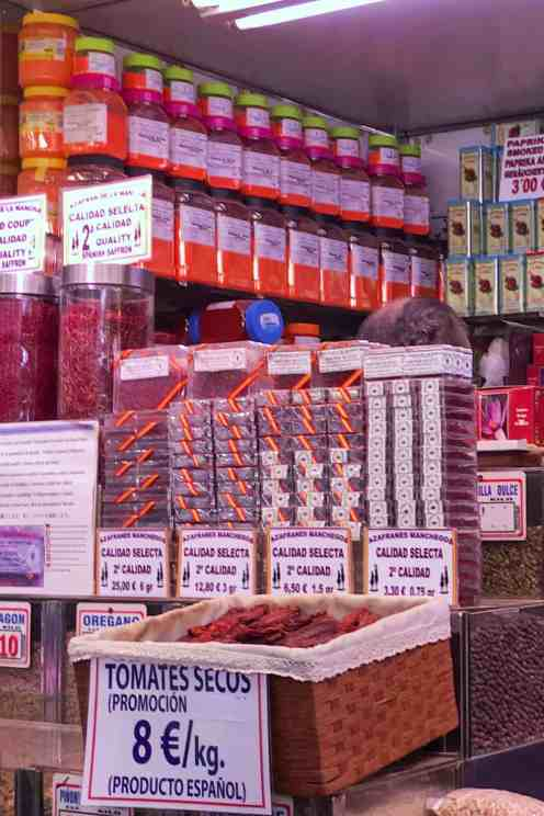 Shop with paprika boxes, dry tomatoes in a basket and price tags in Valencia