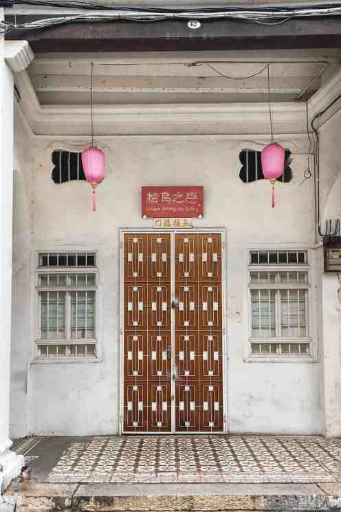 Chinese shophouse with wooden door with grates and two white windows and two pink lanterns