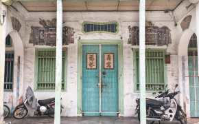 Chinese shophouse with green door and two green windows with two columns
