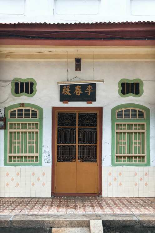 Chinese shophouse with wooden door and two green windows