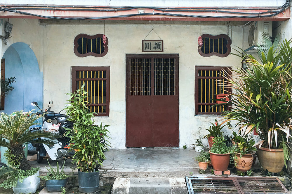 Chinese shophouse with red wooden door and two red windows