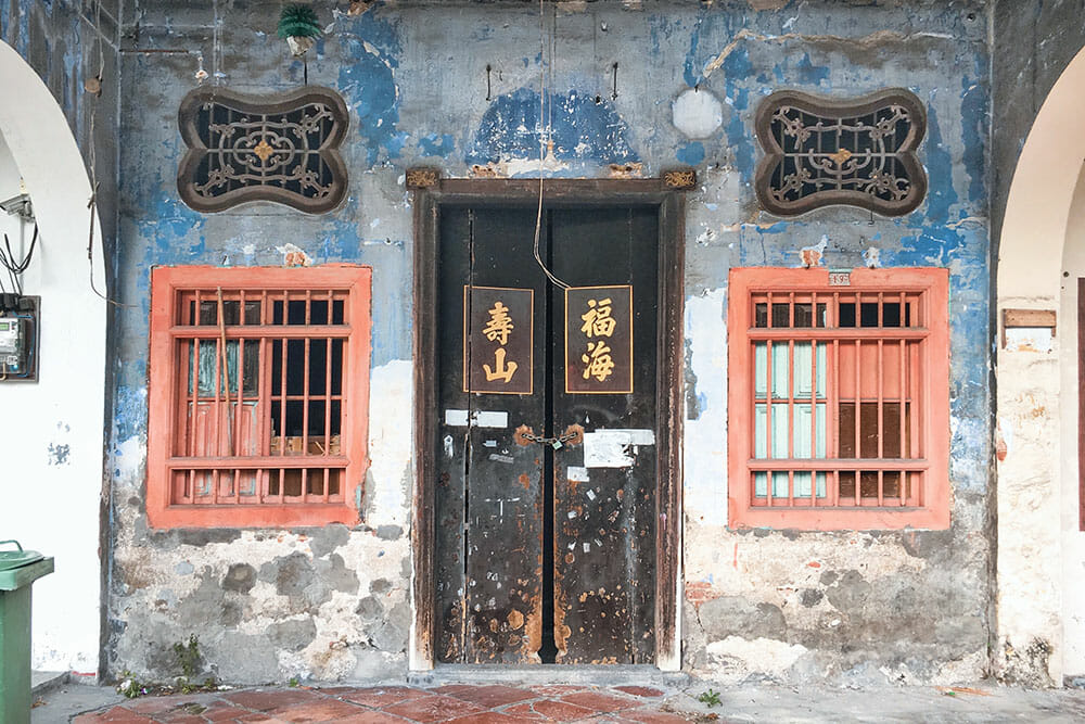 Decayed blue Chinese shophouse with black door and two red windows