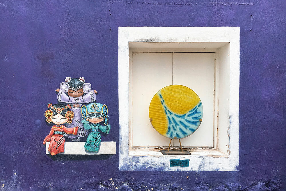 Cute dolls painted on a purple wall next to a white window with a yellow and blue disk