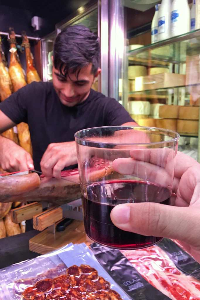 Man carving serrano ham in a shop and hand holding glass of red wine in Valencia