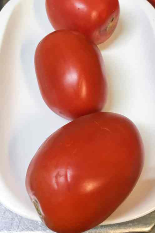 Three roma ripe tomatoes on a plate