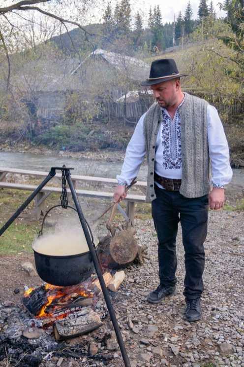 Man making polenta in cauldron in Romania