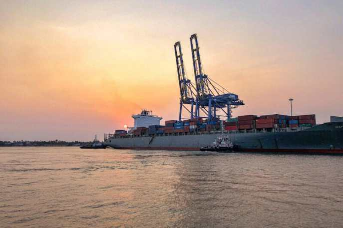 Sunset over a cargo ship moored in Kochi