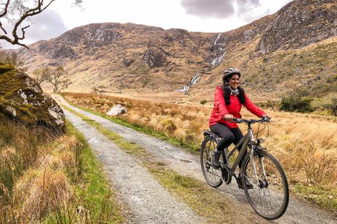 Cycling in Glenveagh National Park with mountains and waterfall in the background
