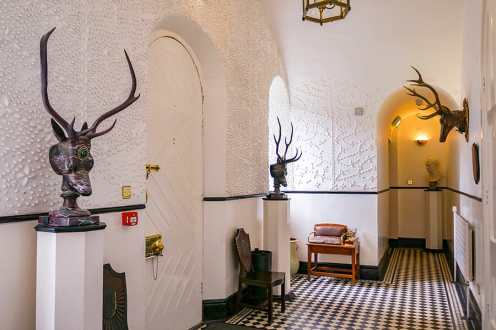 Hallway in Glenveagh Castle with stone-carved deer heads on pedestals and on the wall