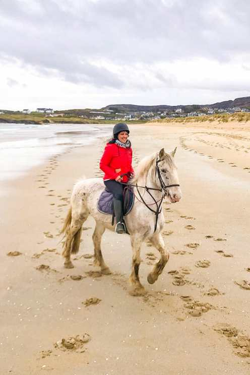 Horse riding a white horse on Dunfanaghy Beach in Donegal