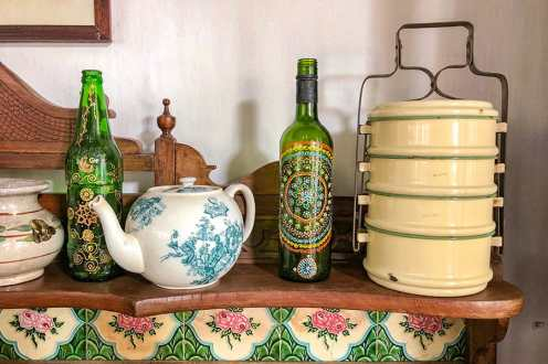 Display of old fashioned tea pot, tiffin box and decorated bottles
