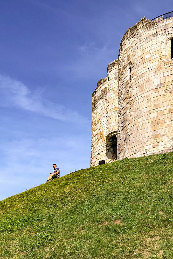 Partial view of Clifford's Tower with man sitting on grass slope
