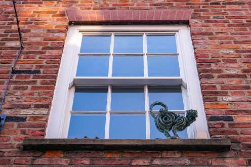 Cat statue on the ledge of a white window on red brick wall