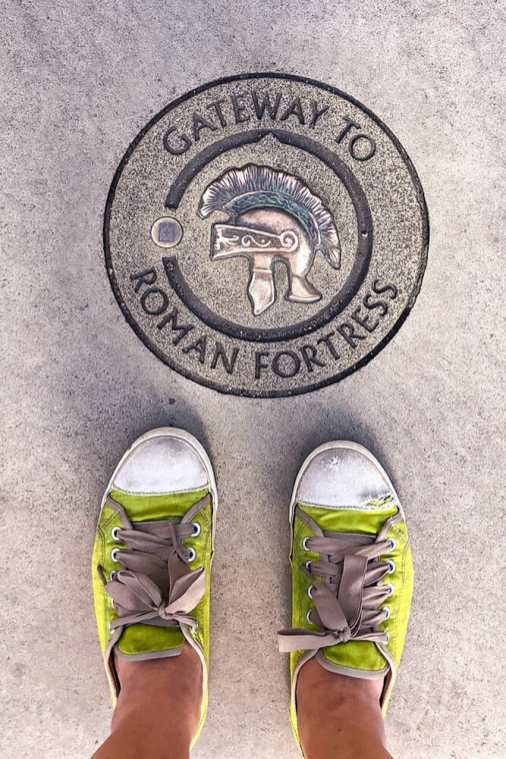 My feet in lime green plimsolls next to a marking on the ground reading Gateway to Roman Fortress