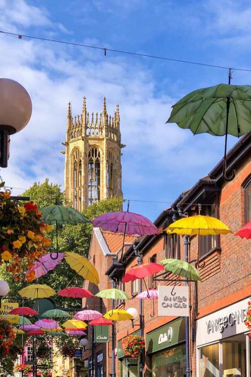 Sunny street with colourful umbrellas as cover with a Gothic church in the background