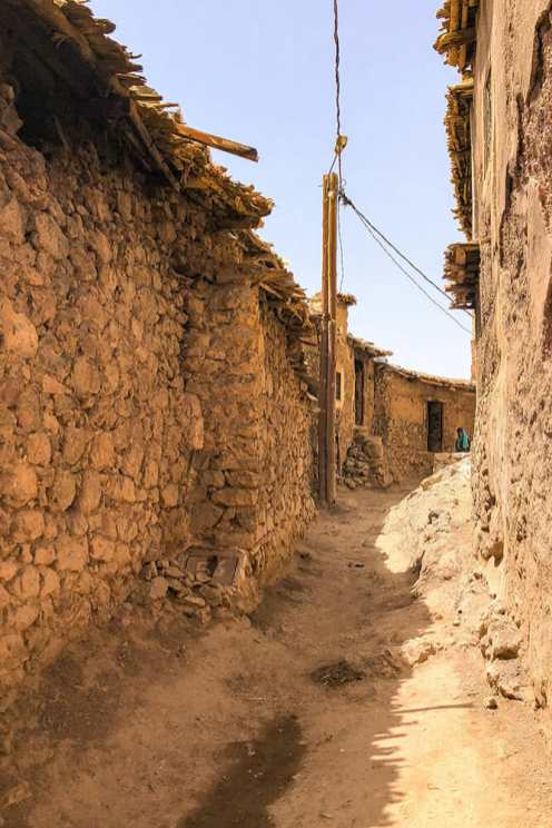Narrow street in a Berber village with walls either side made of stone and mud