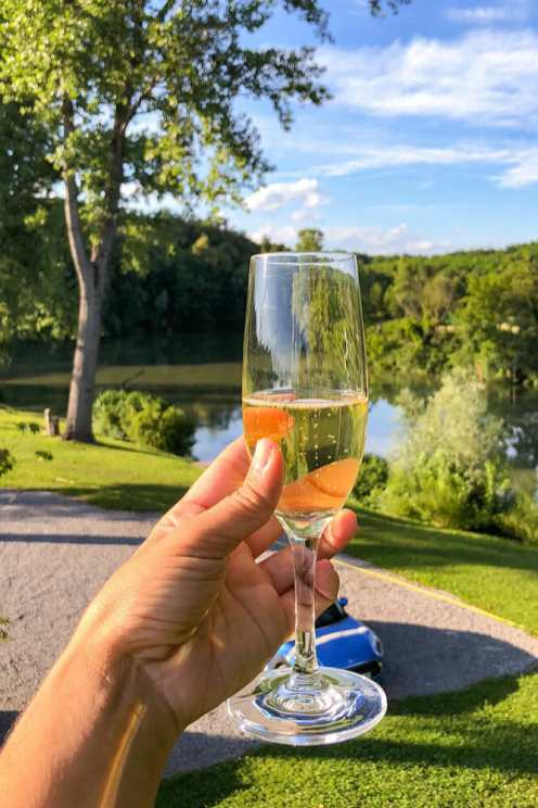 Holding a glass of sparkling white wine with the river in the background