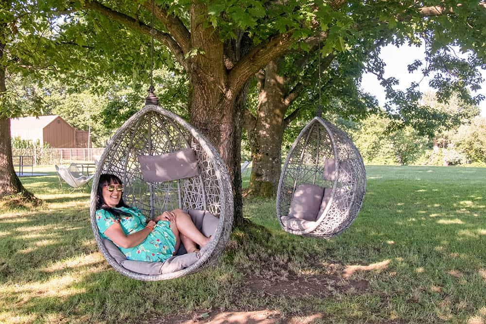 Slouching in an egg chair hanging from a tree