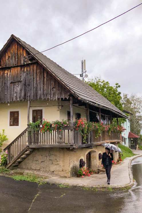 Walking past a wood-cladded house in the village of Drasici in Bela Krajina, Slovenia