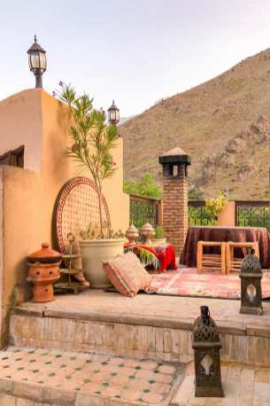 Terrace with a potted tree, lanterns, a carpet and cushions by a chimney