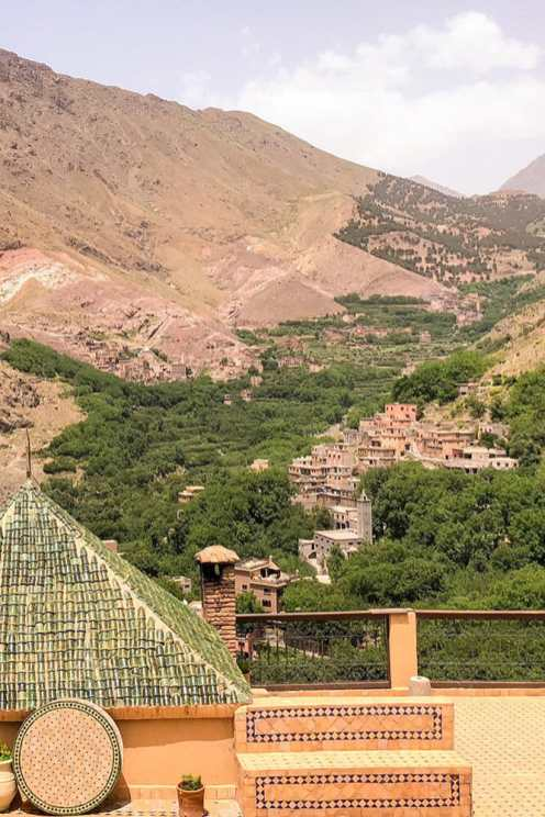 View from the Kasbah of a village on the side of the mountain with a lot of vegetation around