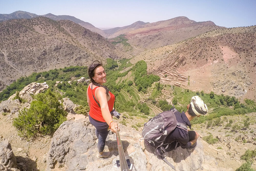 Standing on a rocky outcrop taking a selfie with the view of the Azzadene valley and the mountains