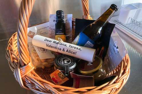 Basket with local produce like beer, oil, biscuits and a letter