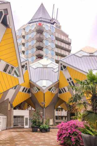 Courtyard surrounded by yellow cube houses and a pointing tower in the background