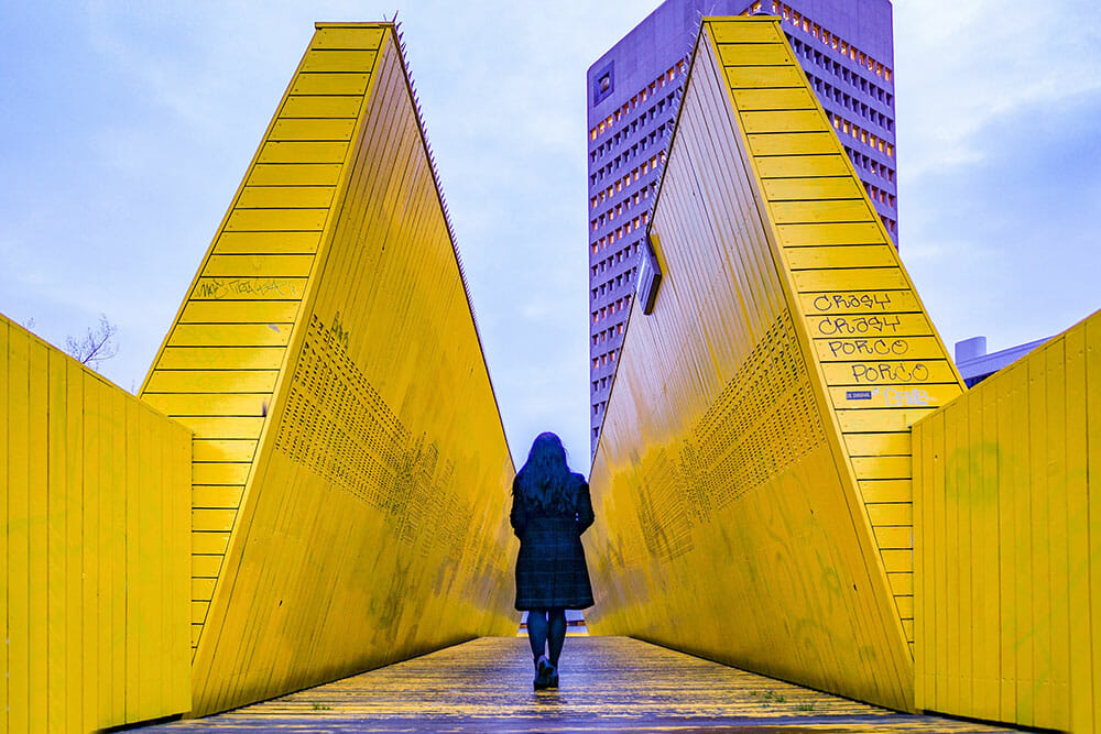 Person standing in between two tall yellow wooden panels creating perspective