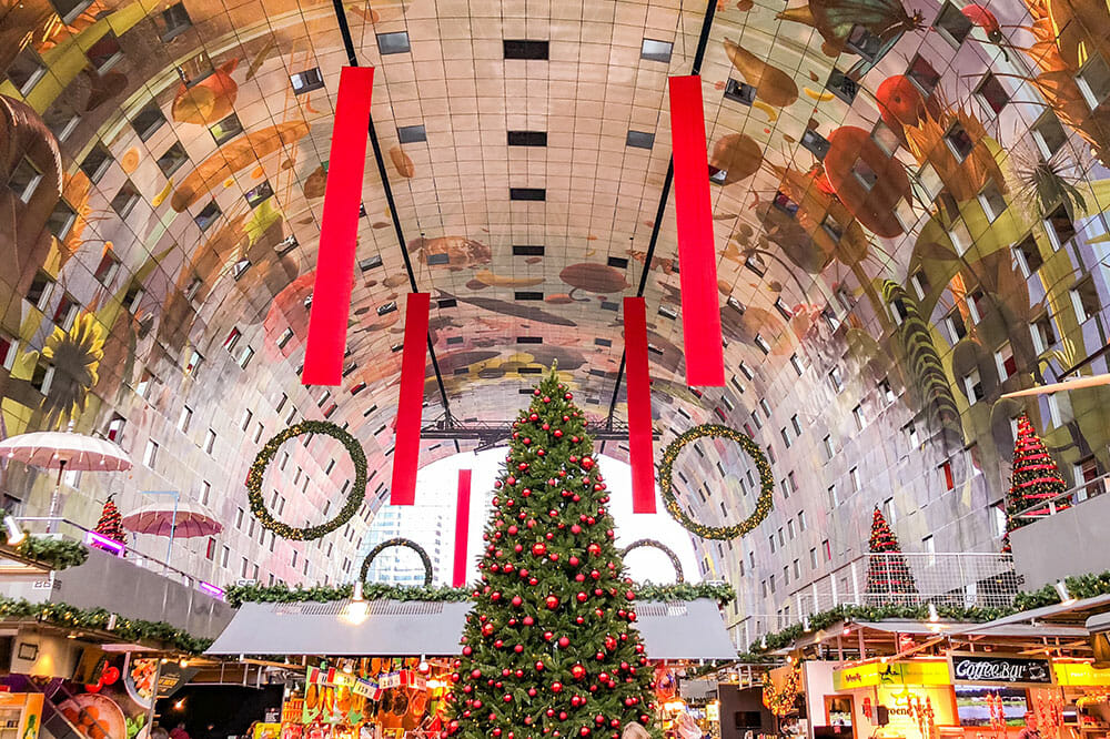 Arched ceiling painted with fruit and flowers above food stalls and a Christmas tree