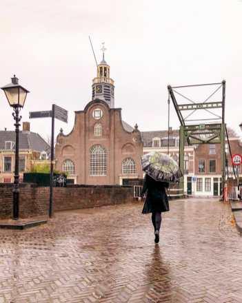Crossing the bridge towards church with umbrella on a rainy day