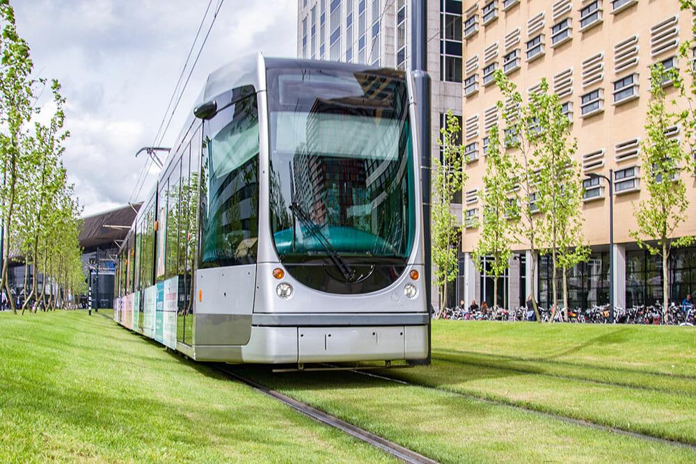 Tram going over tracks on green grass
