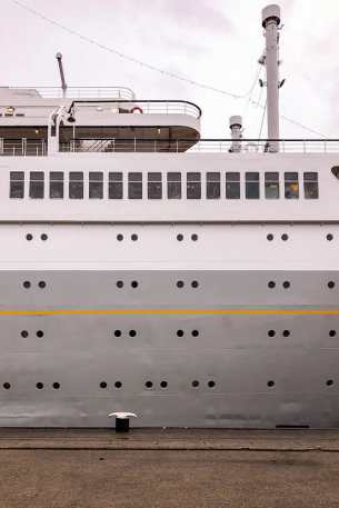 Porthole windows on the side of a grey and white ship