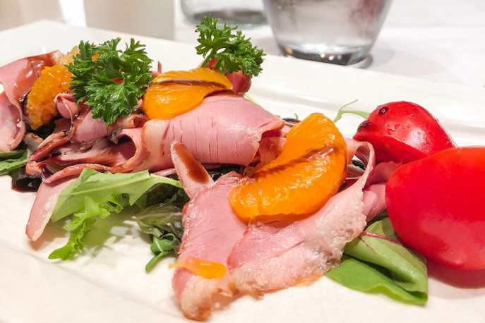 Slices of smoked duck with orange segments over salad leaves