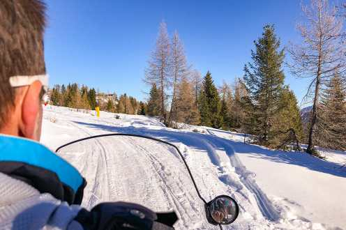 View of the snow road from the back of a snowmobile