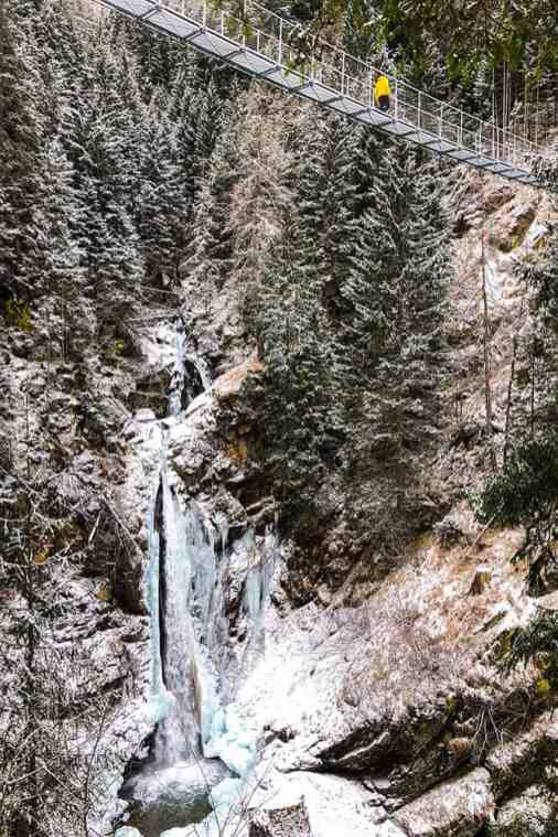 View of a half frozen waterfall with a suspension bridge above it
