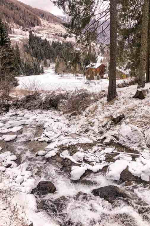 River going through rocky bed with fields around covered in snow