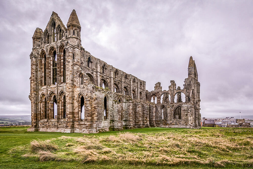 The ruins of a medieval abbey on a field of grass