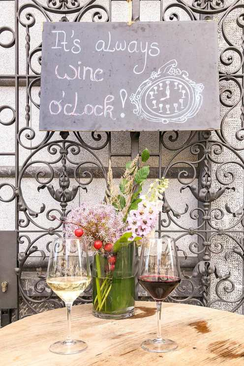 Two glasses of wine, one white and one red, with a flower vase and a sign reading 'it's always wine o'clock'