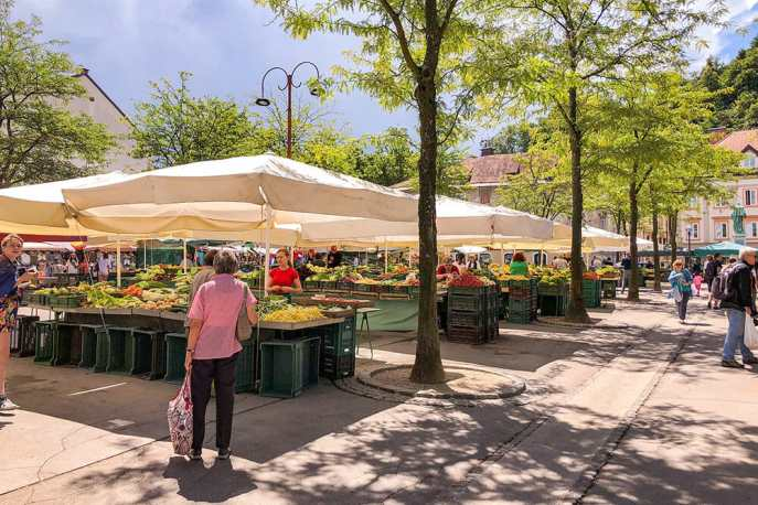 Outdoor market stalls selling fruit and vegetables covered with parasols