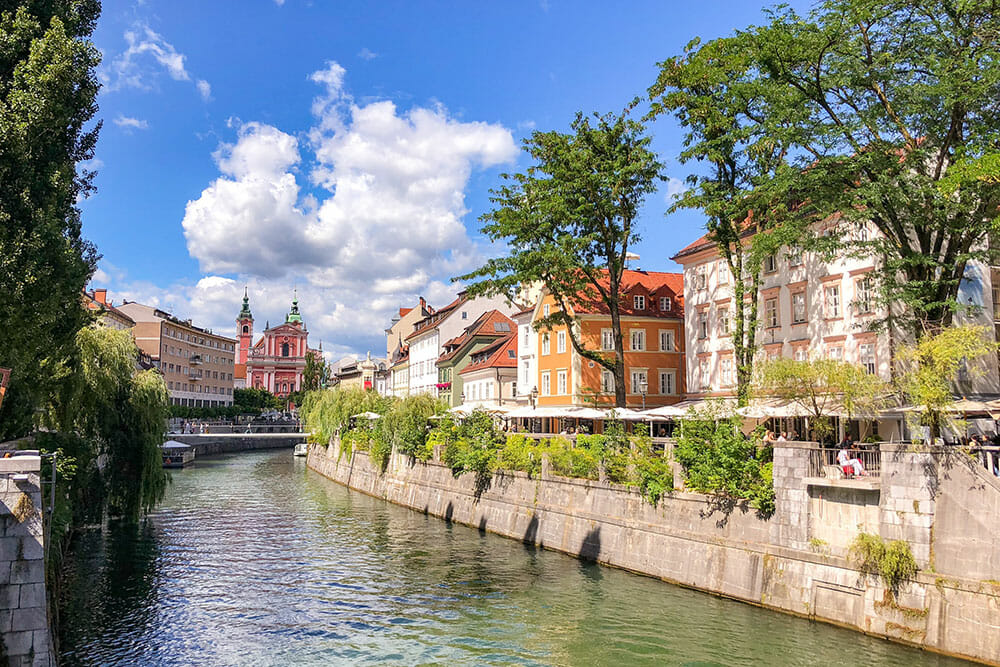 View of Ljubljana river with trees and colourful buildings along the banks