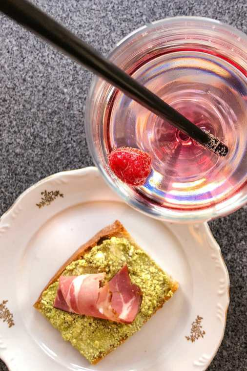 Slice of bread with green paste and ham on a plate, and glass with pink sprizter with raspberry