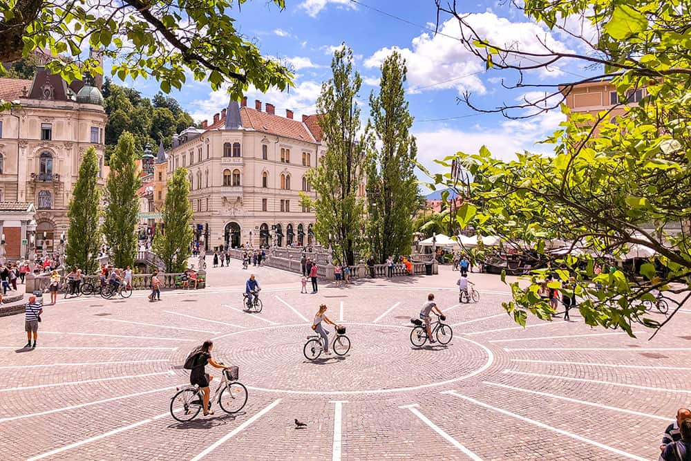 Cobbled square with trees and people on bicycles