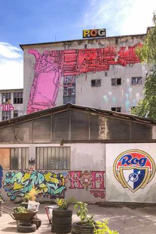 Murals on an abandoned factory wall depicting the ROG logo and a pink gun