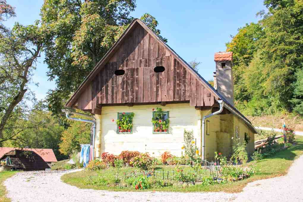 Traditional Slovenian house with wooden shiplap on the gable and small garden at the front